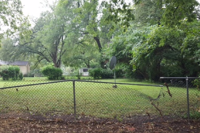 chain-link-fence-bent-and-chain-links-falling-off-of-metal-poles-in-backyard