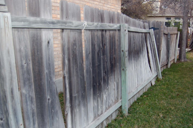 old-weathered-wooden-fence-is-leaning-from-weak-wood-posts